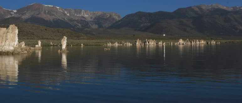 Glassy lake in front of Sierra Nevada with tufa towers reflecting in the morning light with one point of reflection in the lake from a mirror on a hill above.