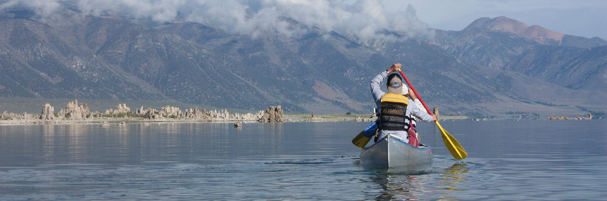 View from behind a person paddling a canoe on Mono Lake with tufa towers and tall mountains shrouded in clouds in the distance.