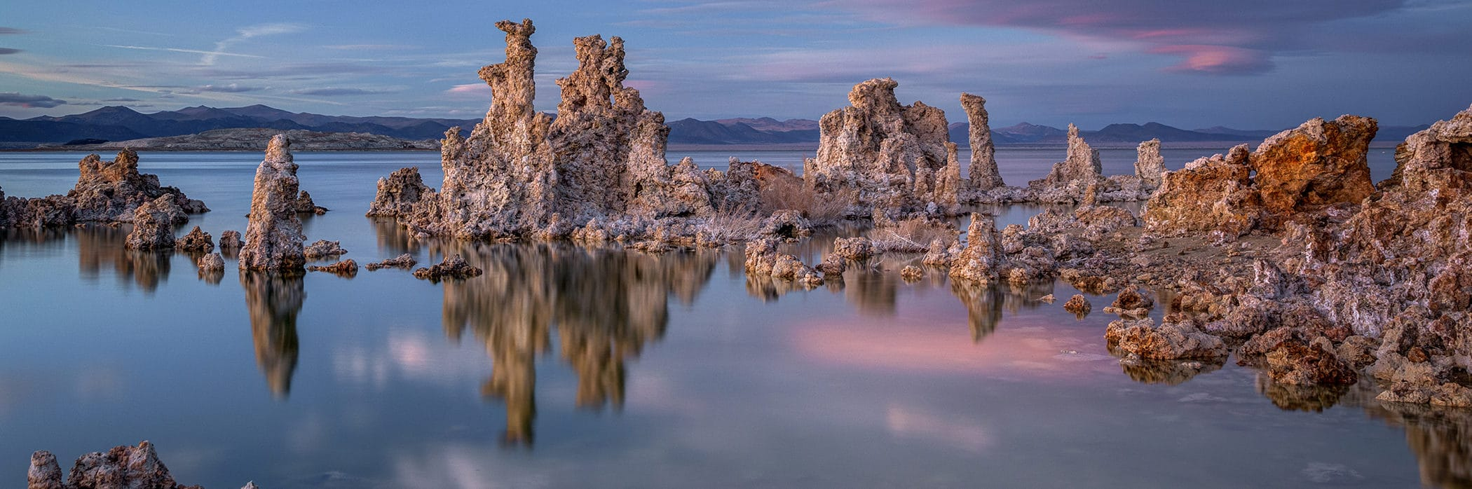 Tufa towers emerging from Mono Lake at sunset with blue skies and unusual clouds lit up in soft pink with beautiful soft light on the tufa towers reflected in the lake's surface, and you can even see some of the rocky shoreline under water.