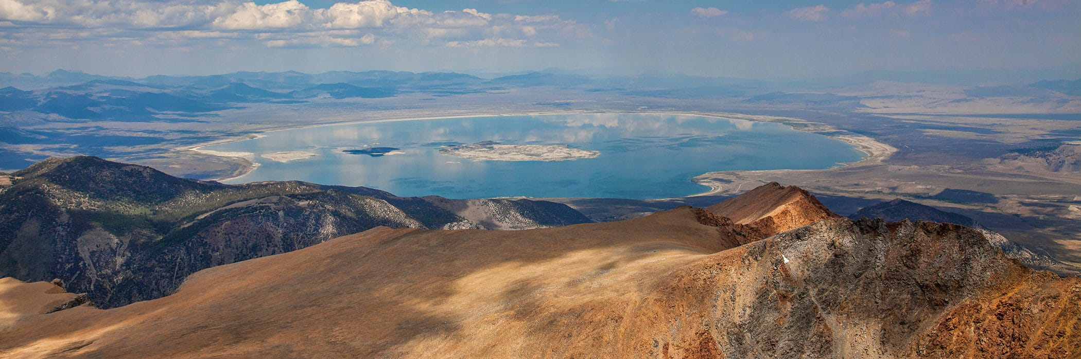 View of almost the entire Mono Lake from a tall mountain peak looking east out over the Mono Basin with Mono Lake's blue glassy reflection of clouds in the sky.