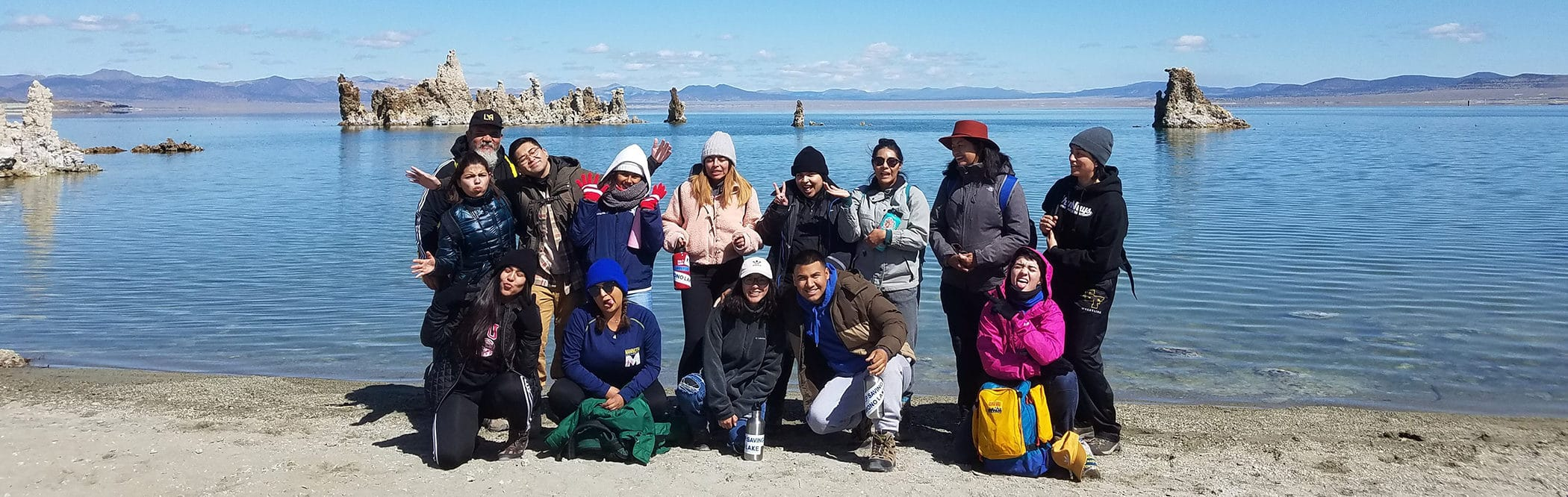 A group of students posing for a group photograph at the shoreline of Mono Lake with the blue lake in the background and tufa towers sticking up from the water and some of the students are making silly faces and gestures.