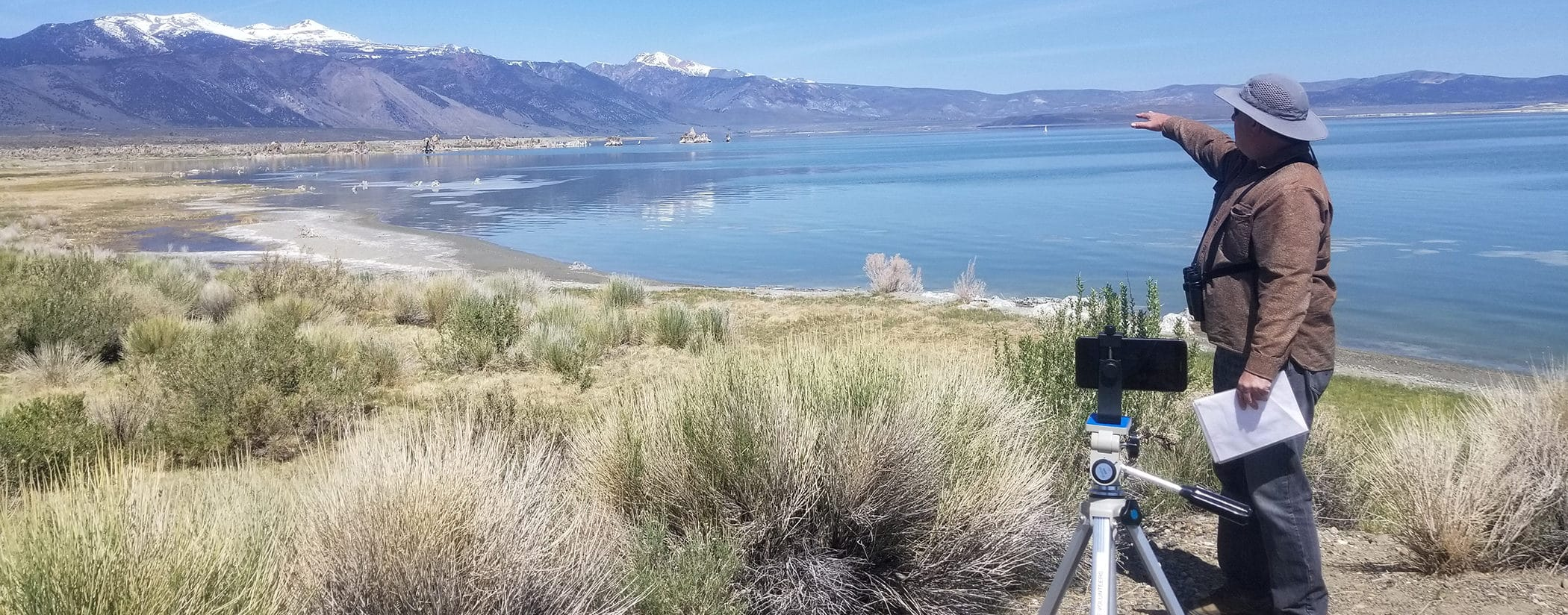 A man is outside with a hat and binoculars pointing out something in the distance while he stands in front of a cell phone mounted on a tripod so he is giving a virtual tour overlooking Mono Lake.