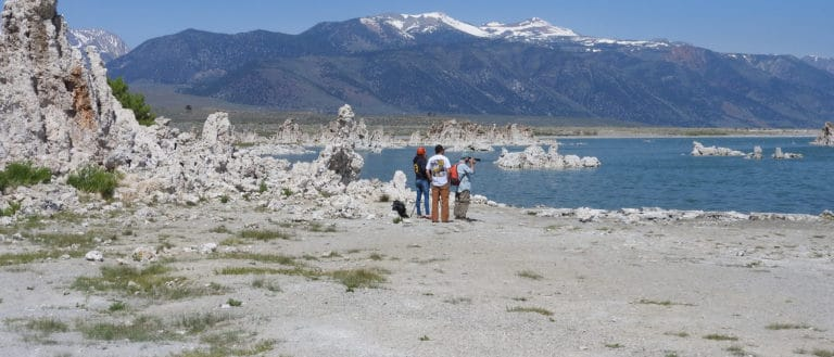 Three people walking along the shore of Mono Lake with tufa towers around them and in the water, with the snowy Sierra Nevada mountains in the background.