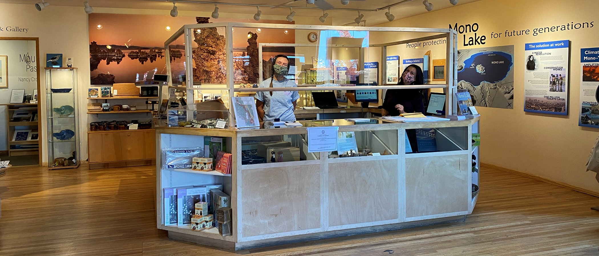 Two people stand inside the warm and welcoming Mono Lake Committee Information Center & Bookstore cash wrap wearing face masks and standing six feet apart while behind a plexiglass barrier and they are surrounded by Mono Lake information on the walls and gifts and books on the shelves.