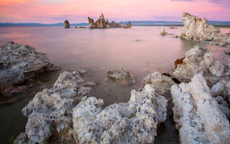 Sunset at Mono Lake with pink hues in the clouds and reflected in the water. with an island made of tufa in the distance and tufa towers framing the foreground.