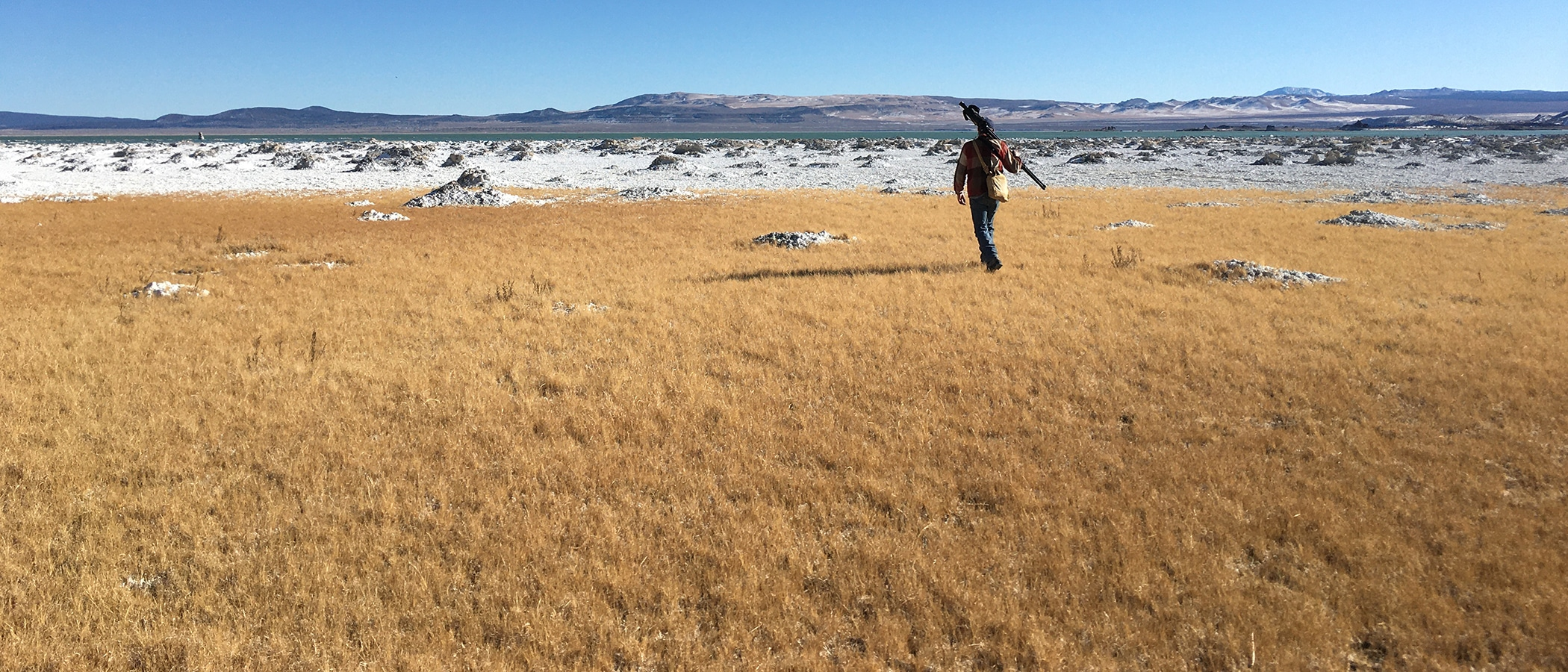 One man walks with a tripod across his back through a golden field of grass towards snow covered rocks on the shore of Mono Lake.