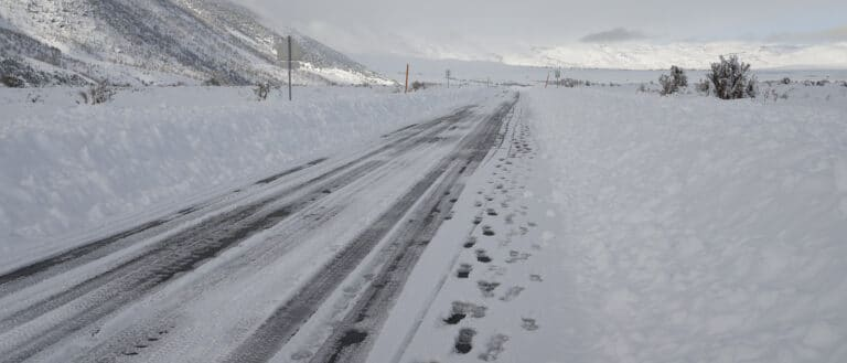 A road is barely visible between huge piles of plowed snow, and stretches into a completely white mountainous landscape.